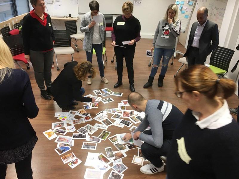 Un groupe debout autour d'un photolangage, des dizaines de photos posées au sol